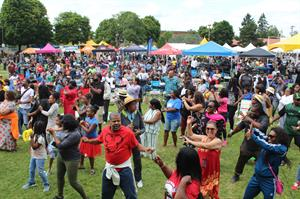 a large, diverse crowd of people gathered in a park for good in the hood festival